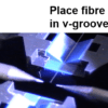 placing an optical fibre in the v-groove of a fusion splicer