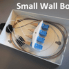 A small wall box for 4 fibres is shown with a cable entry to the left. Fibres are routed clockwise around the inside and spliced to fibre pigtails which end in SC connectors and in line adapters. SC patch cords would connect to the other side of the adapters and then exit the box to connect to LAN equipment